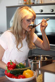 Woman tasting her cooking — Foto de Stock
