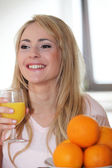Woman enjoying a glass of fresh orange juice — Foto de Stock