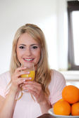 Young woman drinking fresh orange juice — Стоковое фото