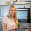Happy woman cooking a meal in the kitchen — Stock Photo