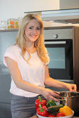 Pretty blond woman preparing a meal — Stock Photo