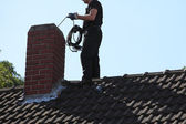 Chimney sweep cleaning a chimney — Stockfoto