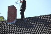 Chimney sweep at work on the roof — Stockfoto