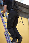 Chimney sweep climbing up to the roof of a house — Stock Photo