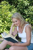 Young woman reading in the garden — Stockfoto