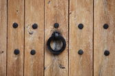 Door handle or kncker on an old wooden door — Stok fotoğraf