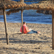 Person reading under a thatched beach umbrella — Stock Photo