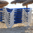 Stack of recliner chairs on a beach — Stock Photo