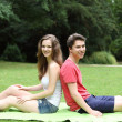 Young teenage couple relaxing in a lush green park — Stock Photo #29796113