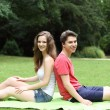 Young teenage couple relaxing in a lush green park — Stock Photo
