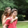 Young man giving his girlfriend a piggyback — Stock Photo
