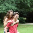 Teenage boy giving his girlfriend a piggyback — Stock Photo