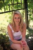 微笑轻松在树荫下的金发女人 — 图库照片