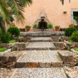Cobbled walkway leading to a garden fountain — Foto Stock