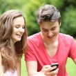 Young teenage couple laughing at an sms — Stockfoto