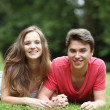 Attractive young couple lying on the grass — Stock Photo