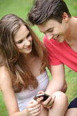 Smiling young teenagers using a mobile — Stock Photo