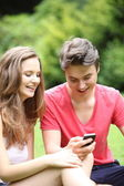 Young teenage couple laughing at an sms — Stock Photo