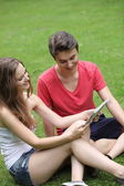 Smiling young girl and boy reading a tablet — Foto de Stock