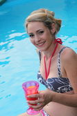 Beautiful woman enjoying a drink at the pool — Stock Photo