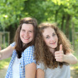 Two teenage students giving a thumbs up — Stock Photo #31093395