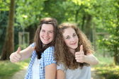 Two teenage students giving a thumbs up — Stock Photo