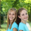 Two happy teenagers standing together in a park — Stock Photo