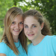 Two teenage girls smiling while posing together — Stock Photo #31131213