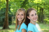 Two happy teenagers standing together in a park — Stok fotoğraf