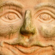 Smiling terracotta face — Stock Photo