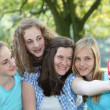 Four attractive teenage girls in a park — Stock Photo