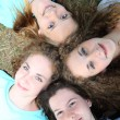 Stock Photo: Four young teenage girls looking up at camera