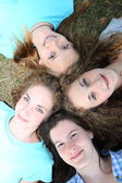 Four young teenage girls looking up at the camera — Stock Photo