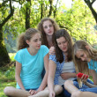 Group of young girls sitting in a park — Stock Photo