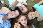 Four happy teenage girls giving thumbs ups — Stock Photo