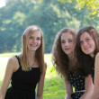 Three attractive happy young teenage girls sitting together — Foto de Stock