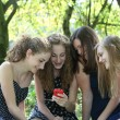 Group of happy teenagers reading an sms — Stock Photo