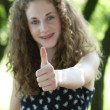 Happy teenage girl giving a thumbs up — Stock Photo