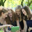 Group of four attractive young teenager working with tablet-pc — Photo