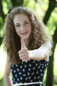 Happy teenage girl giving a thumbs up — Stock fotografie