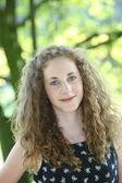 Gülümseyen güzel kıvırcık saçlı kız — Stok fotoğraf