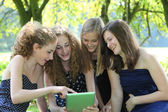Group of four attractive young teenager working with tablet-pc — Stock Photo
