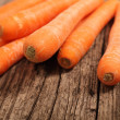Close-up of fresh carrots on a wooden table — Stock Photo