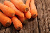 Fresh nutritive carrots on a wooden table — Stock Photo