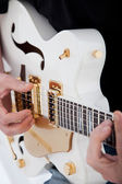 Hands of a man playing an electric guitar — Stock Photo
