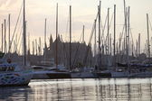 Yachts moored in a marina below a church — Stock Photo