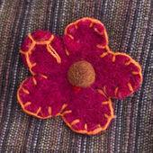 Ornamental flower stitched onto fabric — Stock Photo