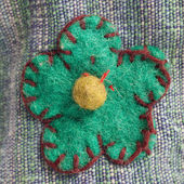 Blue-green flower embroidered onto fabric — Stock Photo
