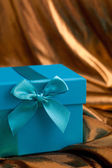 Blue gift box with a bow on gold fabric — Stock Photo