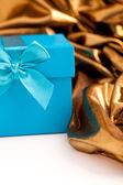 Turquoise gift box with elegant gold fabric — Stock Photo